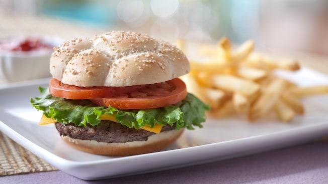 Una hamburguesa con queso, con lechuga, tomate y una guarnición de papas fritas