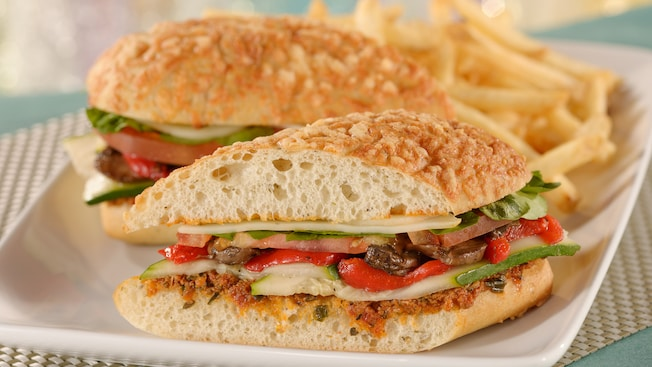 A submarine sandwich with fresh mushrooms, red peppers, zucchini, tomato and watercress next to a side of french fries