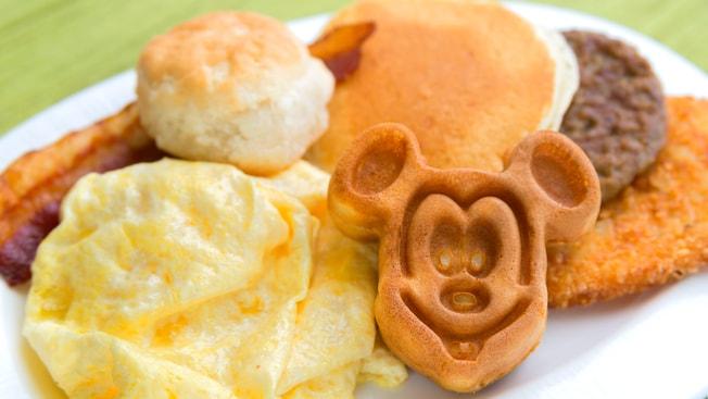 Desayuno con waffle de Mickey, tocineta, huevos revueltos, una hamburguesa de salchicha, croquetas de papas y una galleta
