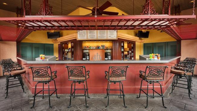 Bar de piscine en plein air, avec des chaises-tabourets en fer forgé, un sol en pierre et un ventilateur de plafond