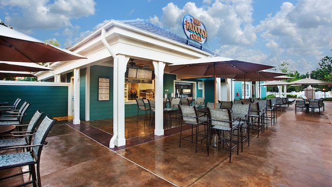 Exterior of The Paddock Grill, with umbrellaed patio tables