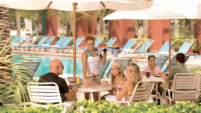Several people seated at poolside dining tables