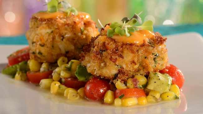 2 garnished crab cakes atop a bed of corn, cherry tomatoes and avocado chunks
