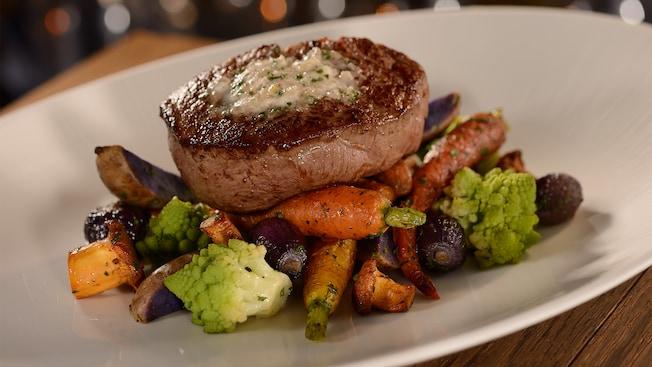 A steak served atop roasted vegetables