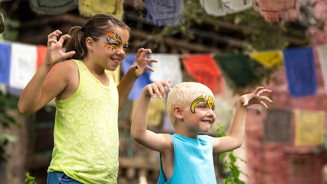 A young female Guest and her even younger brother smile while they pose in ferocious face paint
