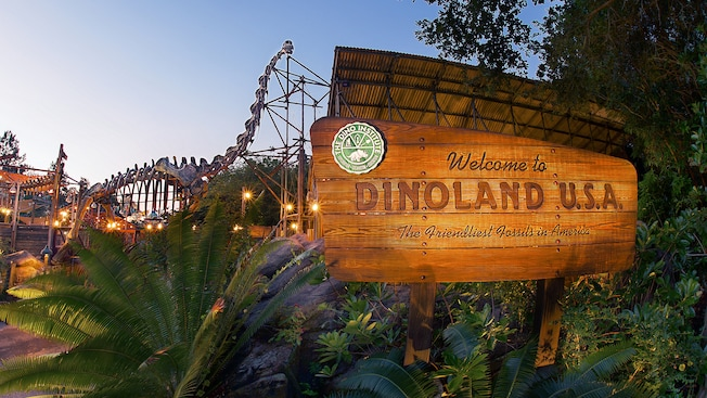 A wooden sign in front of dinosaur-themed attractions reads Welcome to Dinoland U.S.A.