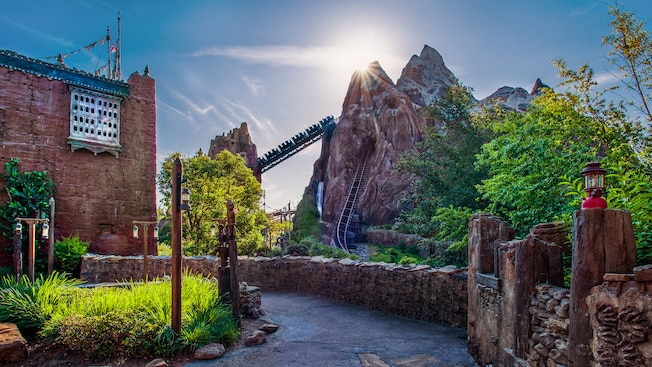 A roller coaster ascends a track between a castle and a replica of a mountain peak