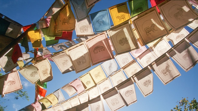 Multiple strings of pennants filled with  jungle animals crissscross through the air
