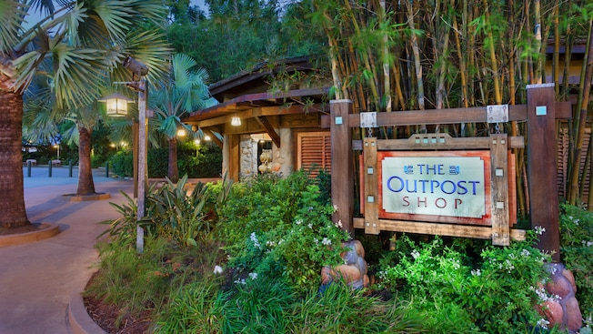 A hanging wooden sign in front of bamboo trees identifies the Outpost Shop