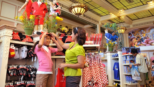 Em uma loja repleta de roupas e produtos Disney, uma mãe ajuda sua filha a experimentar um chapéu da Minnie Mouse