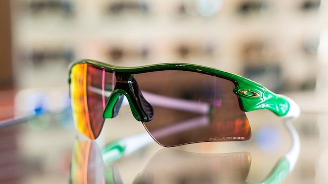 A pair of colorful Oakley sport sunglasses on a counter within the Apex by Sunglass Hut shop