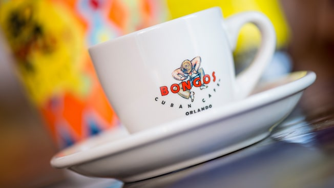 Una taza de café con el logotipo de Bongos Cuban Café Orlando sobre un platillo, fotografiada desde un ángulo inclinado