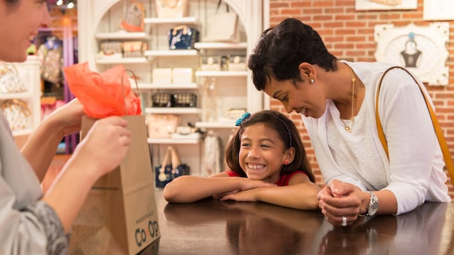A mother and daughter lean against a counter as they watch a saleswoman bag their gift