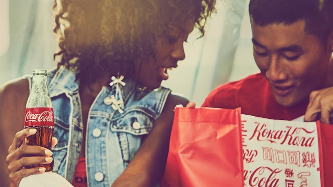 A woman holding a bottle of Coca Cola sits next to her male friend as they both peer into a Coca Cola Store shopping bag