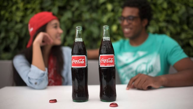 Two Coca Cola bottles with the caps off, rest on a table in front of a young couple