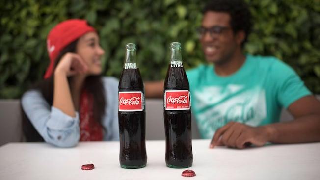 Dos botellas de Coca-Cola destapadas sobre una mesa frente a una pareja joven