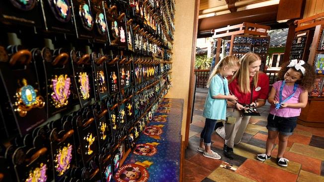 Un membre de l'équipe aide 2petites filles à choisir des épinglettes à côté d'un grand présentoir mural rempli d'épinglettes