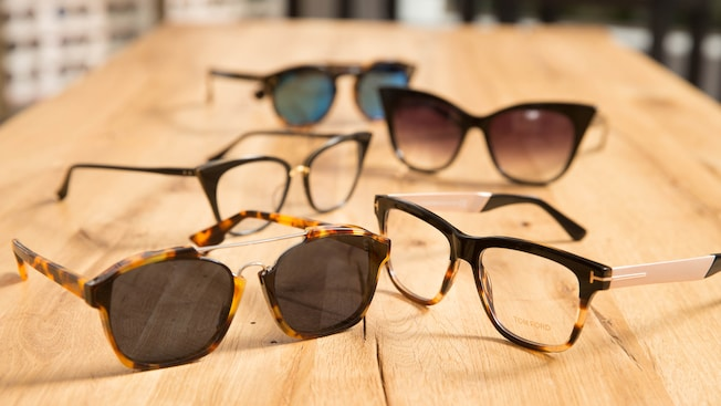 Cinco pares de lentes sobre un mostrador de madera en Edward Beiner Purveyor of Fine Eyewear