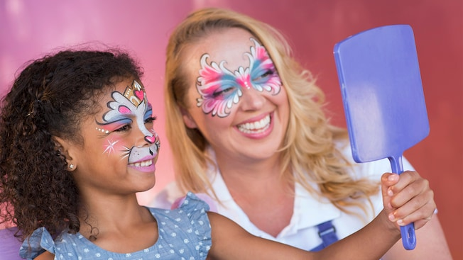 A young girl holds up a mirror to inspect her makeup at the Face Painting by Enjoy Your Face kiosk at Disney Springs as her face painting artist looks on
