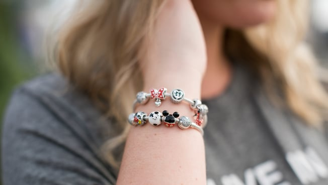 A woman with a bracelet made of Disney themed charms