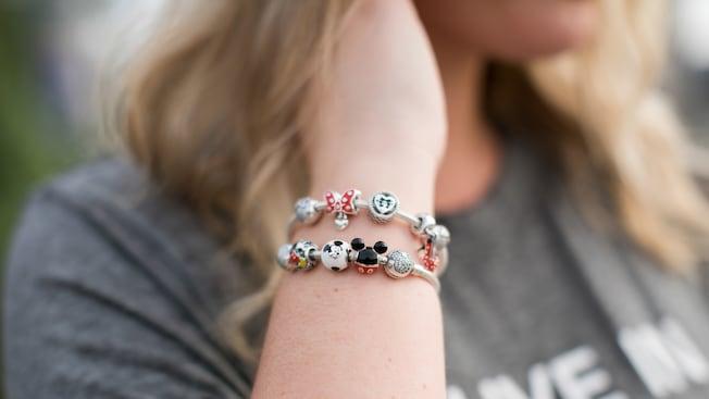 Une femme avec un bracelet composé de breloques sur le thème de Disney