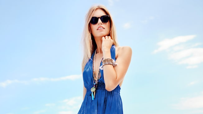 A woman wearing sunglasses models a sundress, bracelet and necklace against a blue sky backdrop