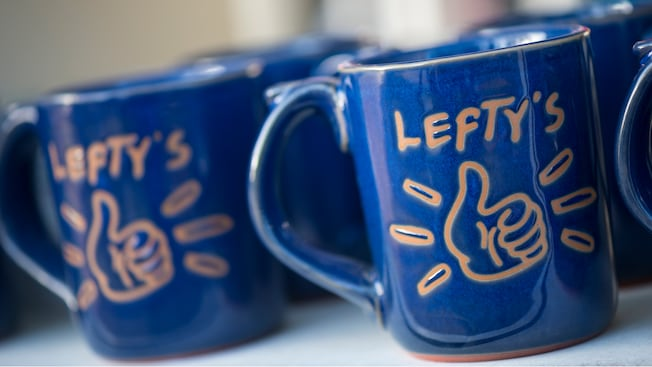 Logo terra-cotta left-handed mugs on a shelf within Lefty's The Left Handed Store at Disney Springs