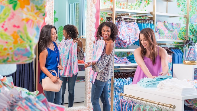Three young female friends shop inside the Lily Pulitzer boutique