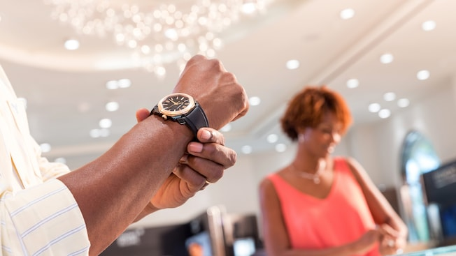 A man tries on a watch while a female shopper glances into a display case