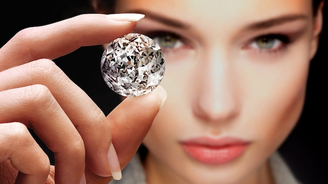 A woman holds a large diamond between her fingers