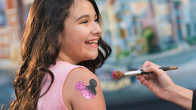 A girl getting a Mickey ears silhouette with glitter painted onto her upper arm