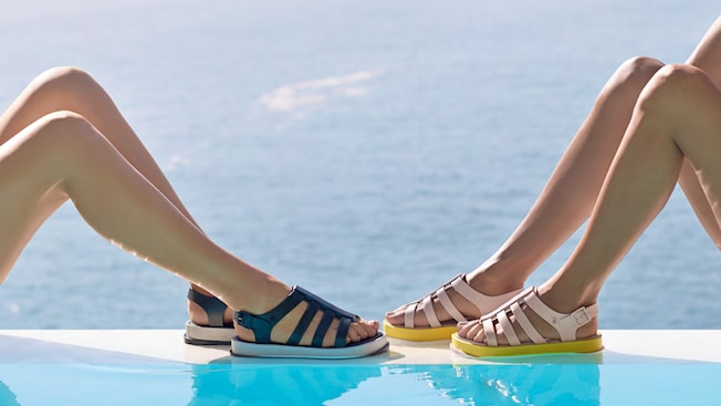Melissa sandals in different shades worn by 2 models against an ocean beach backdrop