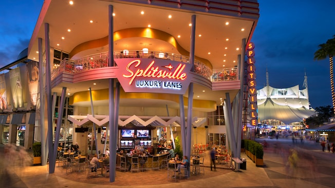 Exterior of two-story Splitsville Luxury Lanes at Downtown Disney West Side lit up at night