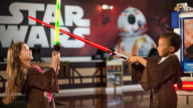 A young girl and boy play dressed as younglings play with light sabers