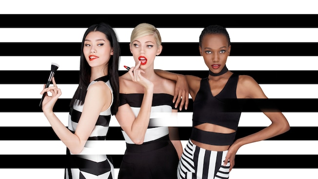 Three women stand shoulder to shoulder wearing lipstick against a striped backdrop