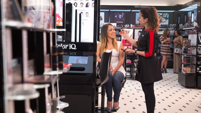 A makeup artist applies bronzer to a female customer's face inside the Sephora boutique