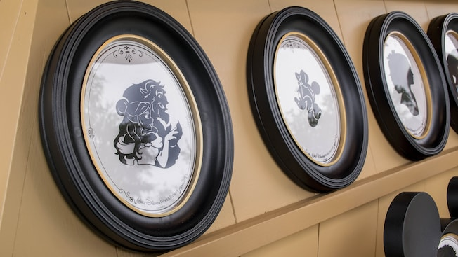 Framed portraits containing silhouettes of Minnie Mouse, Belle, the Beast and other Disney characters