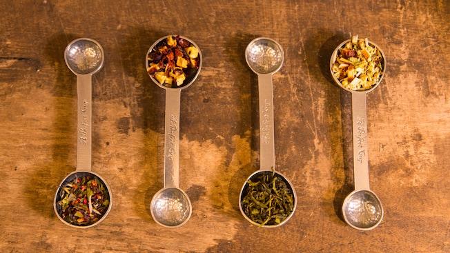 Cuatro cucharas medidoras de doble extremo están ubicadas unas al lado de las otras, y cada una contiene en la parte más grande hojas de diferentes tés