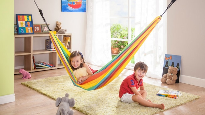 A girl sits in a hammock next to a boy in a sunny room