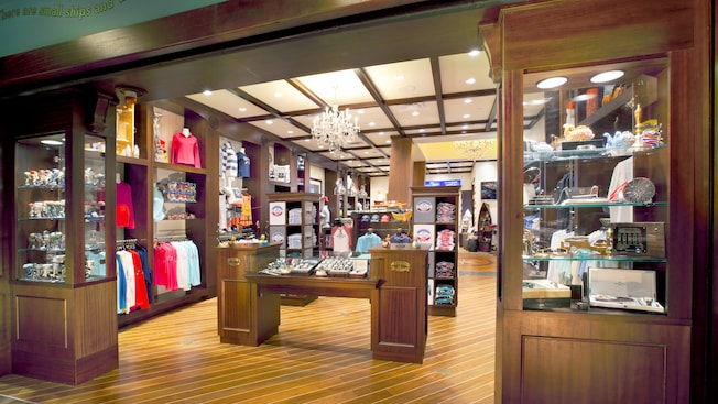 A boutique with wooden floors and cabinets displays clothing, jewelry, gifts and accessories