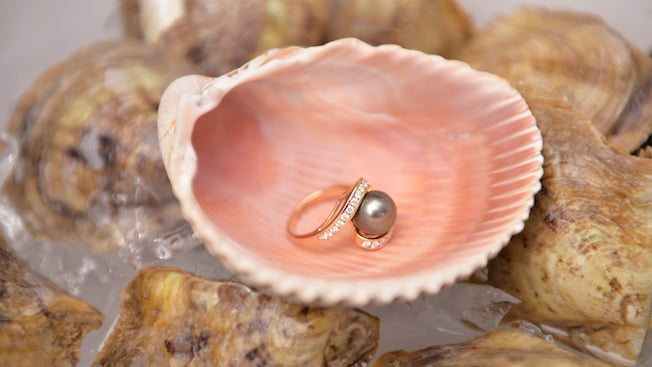 A pearl set in a ring is displayed on a half oyster shell