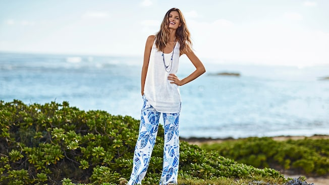 A woman wearing a Tommy Bahama loose fitting cotton tank, beaded necklace and leaf print linen pants at the beach