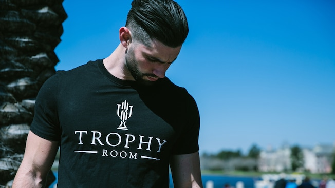 A man modeling a logo Trophy Room T shirt