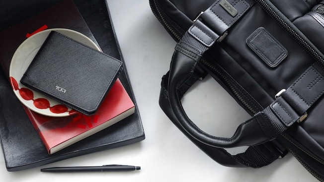 A TUMI wallet rests on top of a small decorative bowl and a book that is placed next to a pen and TUMI laptop bag