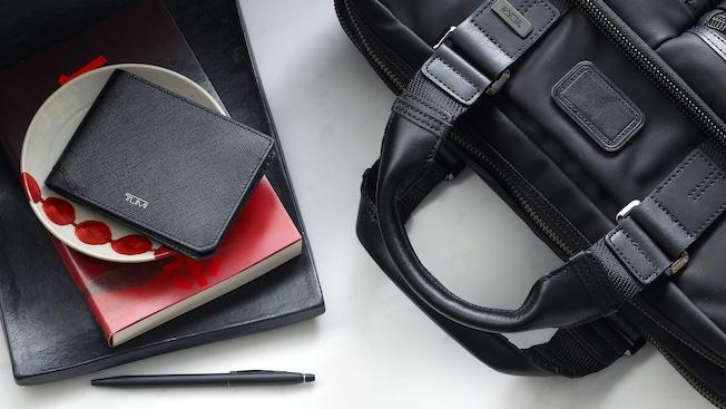 Una billetera de TUMI apoyada sobre un pequeño tazón decorativo y un libro que está colocado junto a un bolígrafo y una bolsa para portátil TUMI