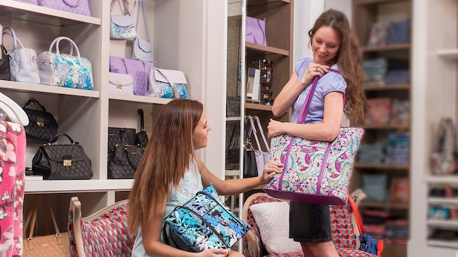 Una mujer joven está sentada en una silla y admira el bolso de Vera Bradley que su amiga carga en el hombro