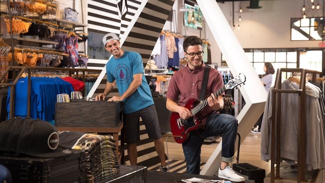 Un joven toca una guitarra de exhibición mientras un amigo lo observa con entretenimiento dentro de Volcom
