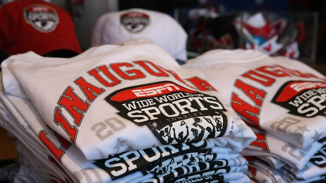 Baseball caps, assorted t-shirts and other featured ESPN Wide World of Sports merchandise on display