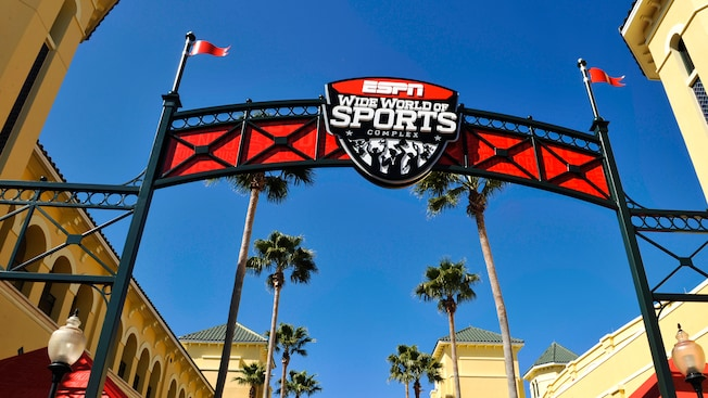 "A red banner sign forms an archway above an entrance that reads: ""ESPN Wide World of Sports Complex"""
