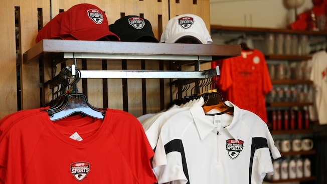 Baseball caps, assorted sweaters and other featured ESPN Wide World of Sports merchandise on display